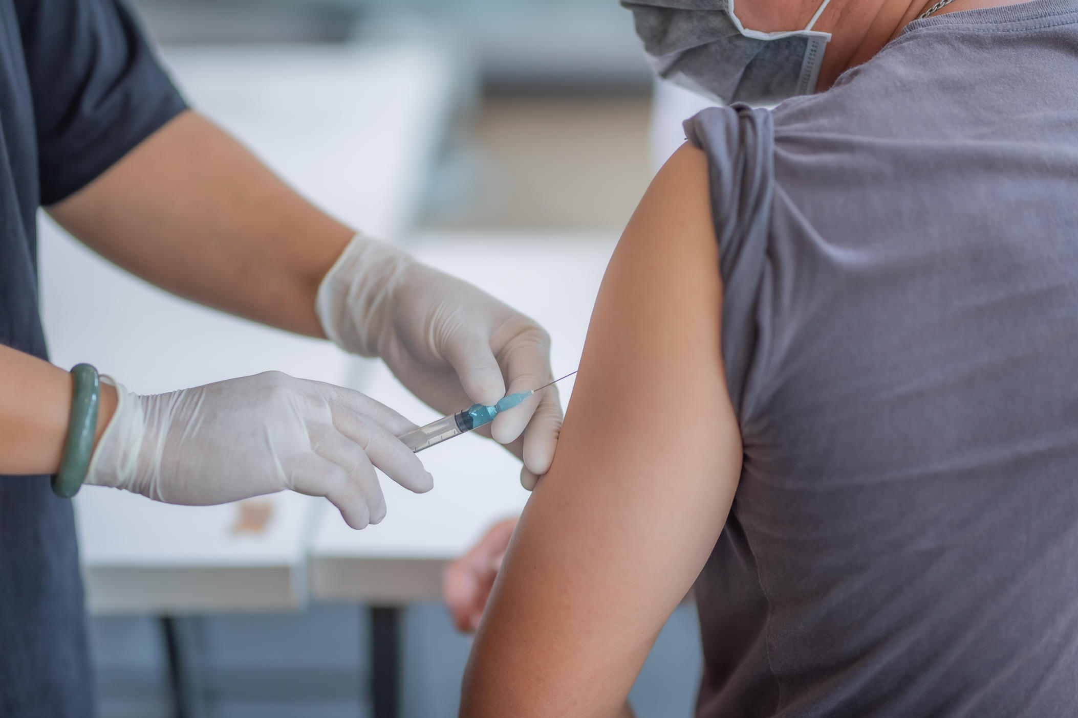 person with sleeve rolled up receiving vaccine