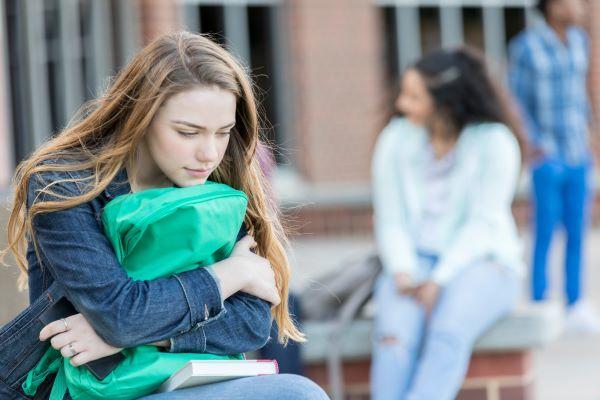 Teenage girl holding backpack